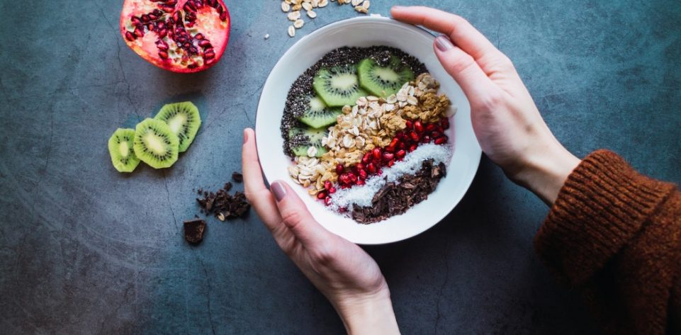 womans-hands-holding-a-smoothie-bowl-with-vegan-ingredients-on-concrete-background-healthy-life-flat_t20_Kv0pmZ